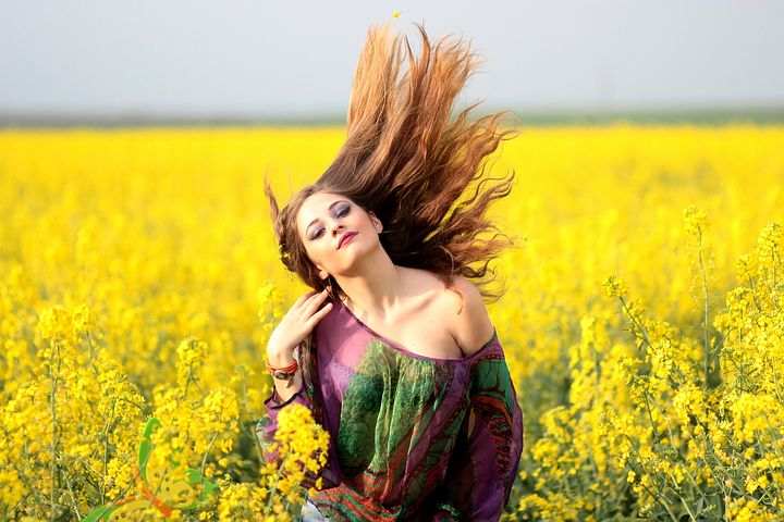 Beautiful girl in yellow flowers farm image